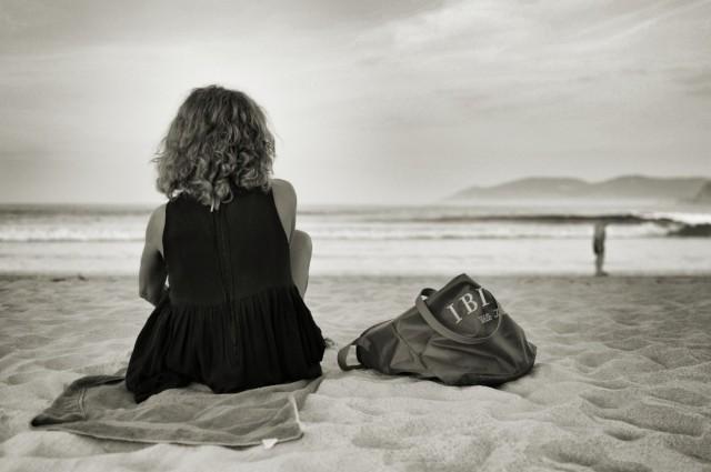 femme-assise-sur-le-sable-au-bord-de-la-plage-1560x1037